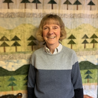 Anneke Larrance stands in front of a quilt, smiling and facing the camera.