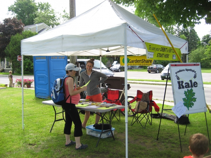 Summer intern Emma Duffany helps a visitor at the Potsdam Farmers Market